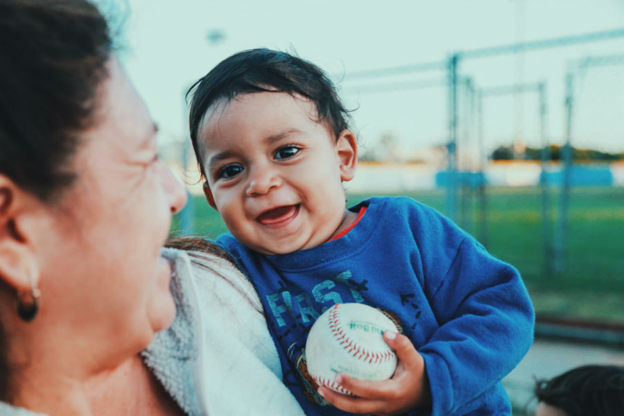 An American boy citizen holding a baseball and smiling