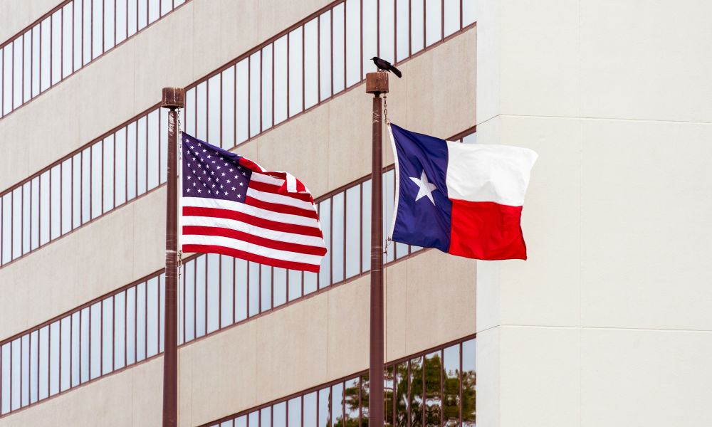 Texas flag and American flag in front of law firm building
